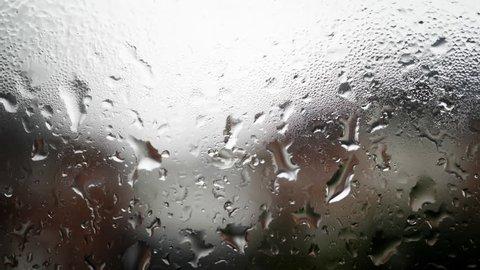 Rain water dripping down a window stock footage. Rain water running down a window in close up background.