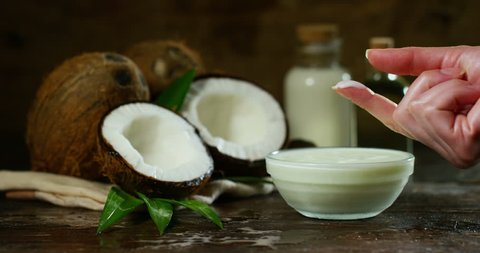Fresh nourishing coconut milk moisturizing cream for hands, face and skin, on a dark wooden background, concept: spa, skincare, beauty, healthy lifestyle, bio products, ecologic products, massage.