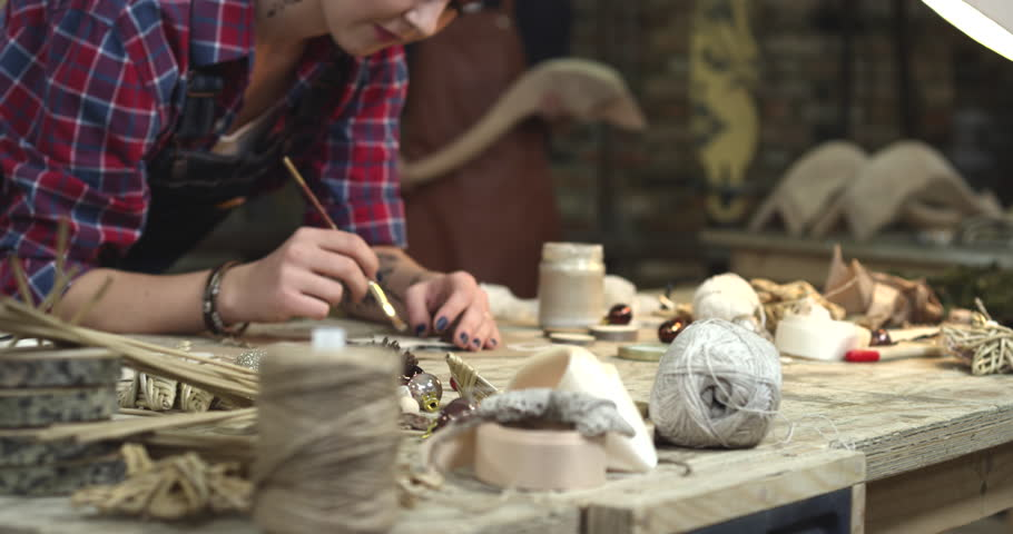 Young hipster paints her handmade toys. We see all the possible things that help her create the handmade stuff/Young Hipster Painting Handmade Goods in her Studio | Shutterstock HD Video #25865702