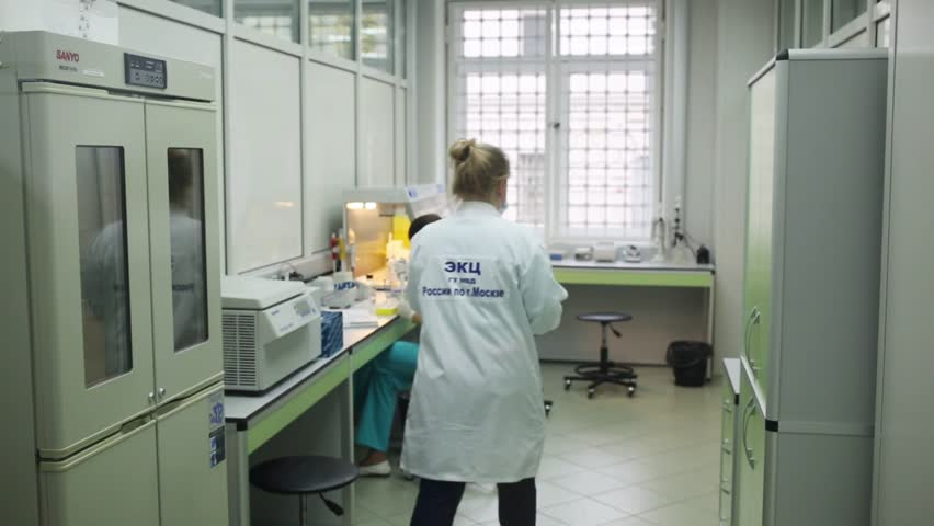 MOSCOW, RUSSIA - SEP 22, 2016: Two women are working in Criminal laboratory at Petrovka 38 on office (DNA isolation). #25881692