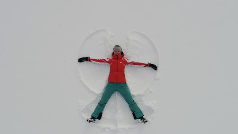 Top view of snow angel. Camera moves out from woman lying in snow and making snow angel