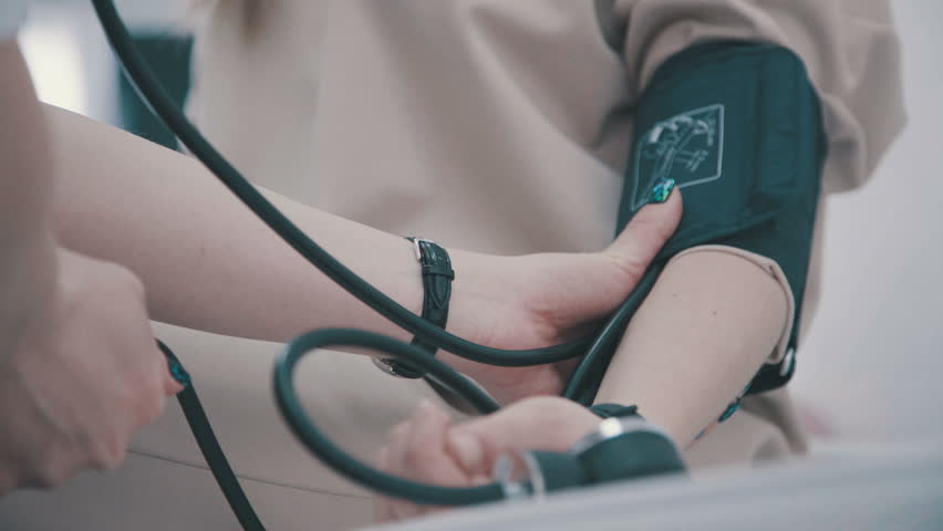 Doctor and patient blood pressure check up - Female patient's arm extended. Doctor checking blood pressure of a patient, he is measuring heart pulses with a sphygmomanometer