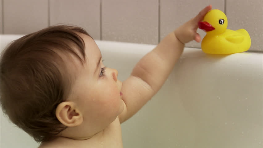 Stock video of child sitting in a bathtub chewing | 2595092 ...