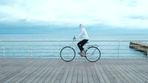 Young woman riding a bicycle in cloudy weather near the sea on wooden embankment