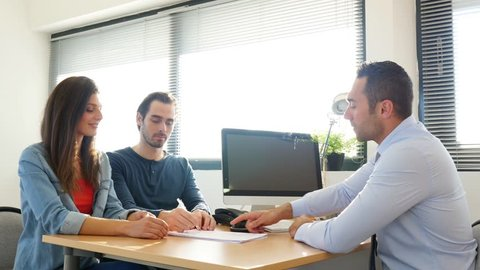 buying agreement contract signature and hand shaking between young couple and professional finance business man in office