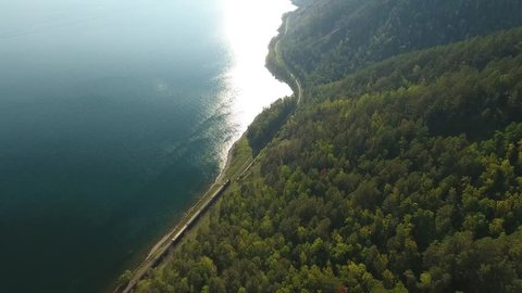 Lake Baikal oldest. Railways private passenger train Russia Siberia. Train ride near the water. Mountains pine forest. Summer sun shines blue water. Aerial video high altitude above lake. 4k