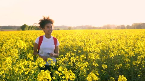 Beautiful happy mixed race African American girl teenager female young woman hiking with red backpack and bottle of water in field of rape seed yellow flowers