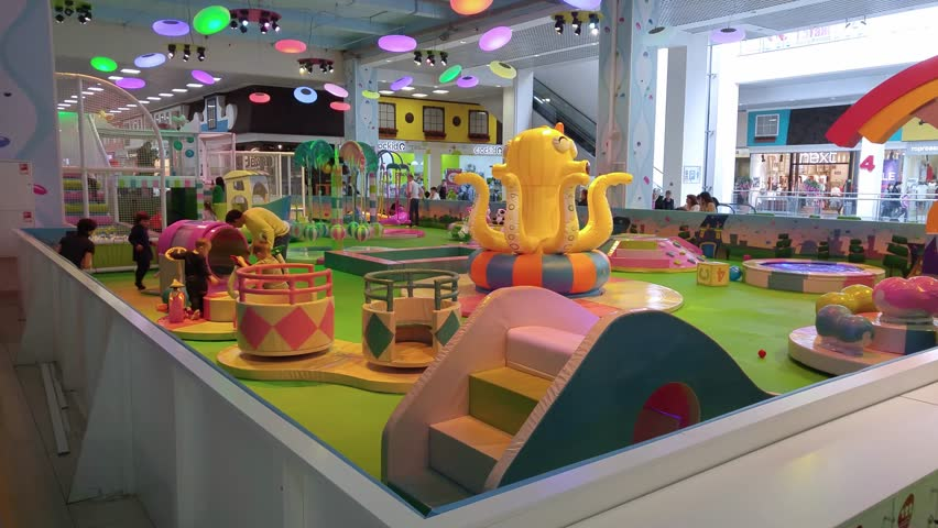 SAMARA - APR, 8, 2016: Children playground with inflatable octopus, carrousel and slide in supermarket Aurora , mobile phone video. Babies in Mall of Aurora can stay in equipped childrens playroom.