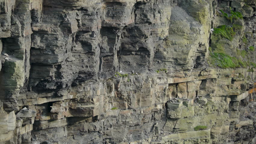 Closer look of the big rocks in Moher Cliffs in Ireland. The magnificent Cliffs of Moher top the list of places to see and things to do in Ireland and are Irelands most visited tourist attraction.