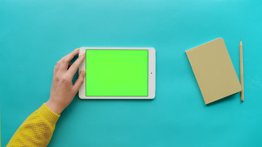 Female hands using white tablet computer with green screen on blue background with daily notebook. Woman scrolling pages, tapping on touch screen, surfing on the internet. Chroma key. Close up shot | Shutterstock HD Video #26050532