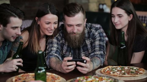 The guy makes a friend company in pizzeria. A company of friends resting in a pizzeria and making selfie on the background of pizza and beer