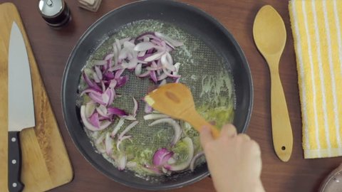 Bird's eye view, close-up woman frying red onions on frying pan, young woman preparing meal at the kitchen table.