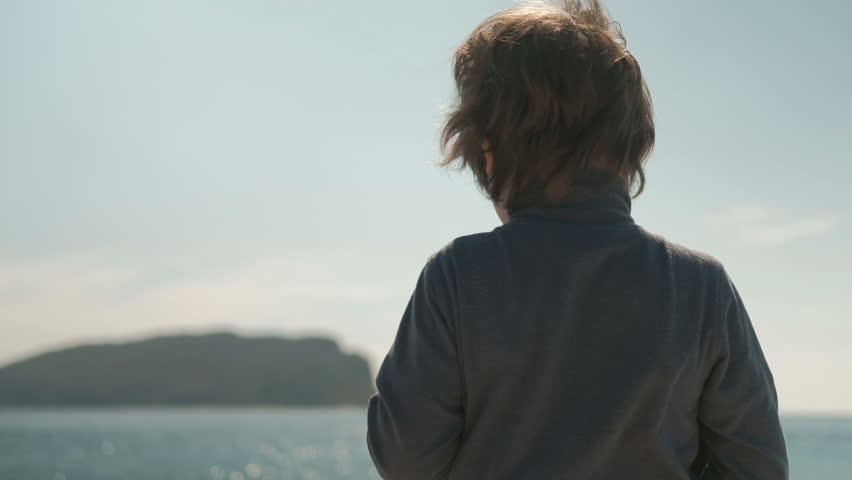 The boy stands with his back on the coast and puts on a big hat. A child in a blue jacket is in front of the sea and pulls a beige hat with large fields on his head.  #26084342