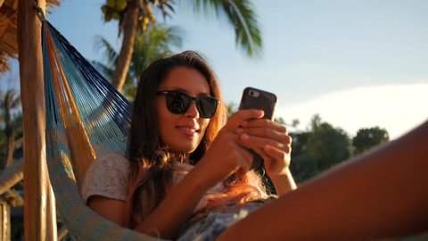 Atractive Young Hipster Girl Using Mobile Phone in Hammock at the Beach near the Sea at Sunset. Koh Phangan, Thailand. HD Slowmotion.