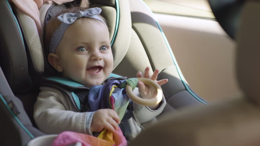 Cute Baby Girl Plays With Toy In Car Seat, She Smiles And Laughs, Ready To Go For A Ride In Family Car