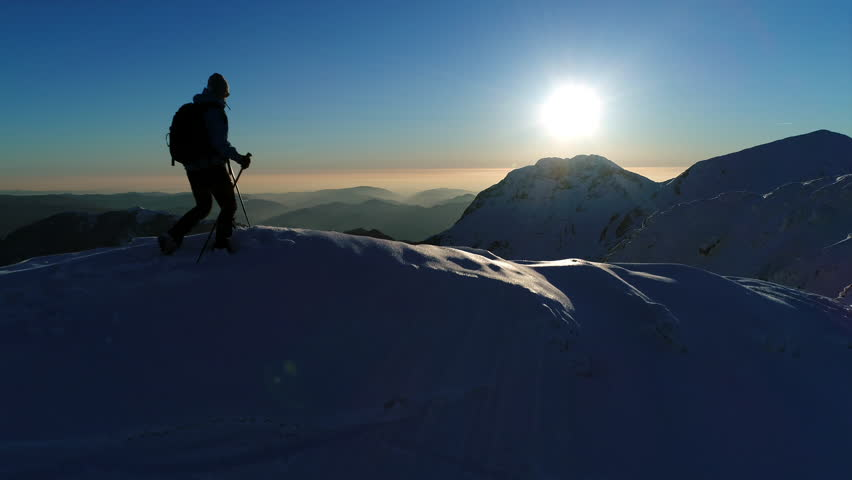 Aerial - Close up shot of young winter hiker arriving on top of snowy mountain peak at sunset