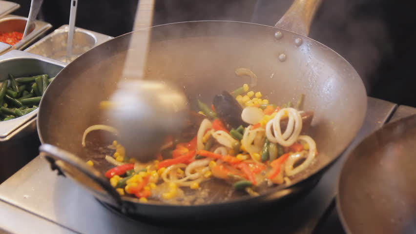 Professional cook is frying mussels and shrimps with vegetables at the street food festival. Roasted prawns and mollusk close up. Cooking process of sea food. Traditional asian food.