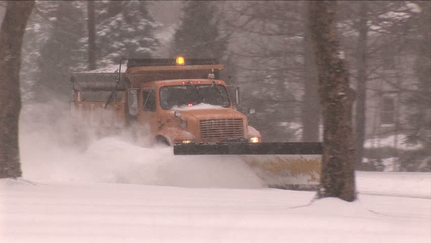NEW ENGLAND - CIRCA JANUARY 2006: City snowplow plowing residential street in snowstorm