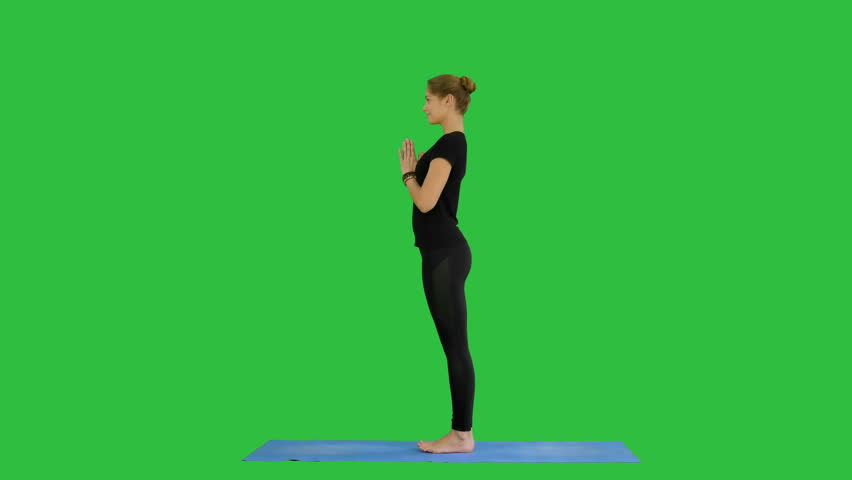 Young woman doing yogic sun salutation pose on mat on a Green Screen, Chroma Key