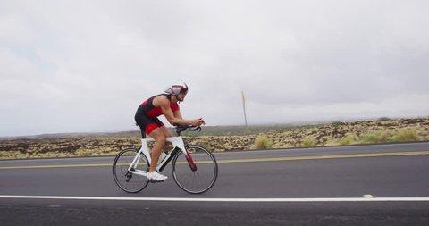 Triathlon cycling - male triathlete biking on triathlon bike. Fit man cyclist on professional triathlon bicycle wearing time trail helmet for ironman race. From Big Island Hawaii. SLOW MOTION RED EPIC