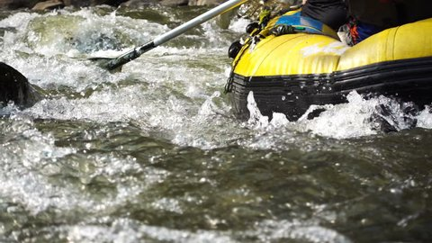 Close-up part of rubber raft with athlete in raging rapids stream.