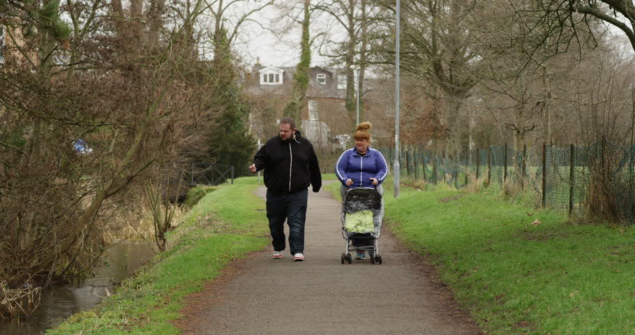 4K Unhealthy overweight parents setting a bad example - smoking cigarettes on a walk outdoors with their baby. Slow motion.