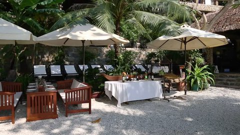 Outdoor cafe on beach ready welcoming guests. Buffet with tables chairs empty plates, glasses and nobody. Sunny day on beach street cafe ready to serve guests. Restaurante outdoor under sun umbrellas.