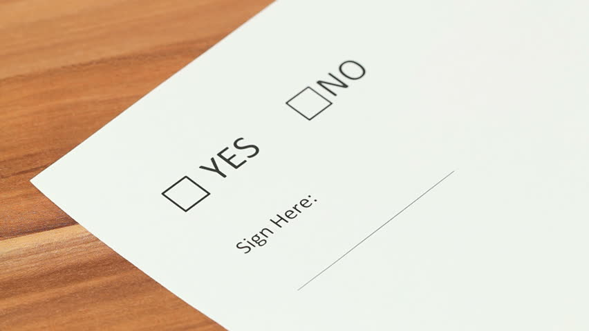 Woman deciding between yes and no checkbox, choosing yes and putting her signature using a fountain pen.