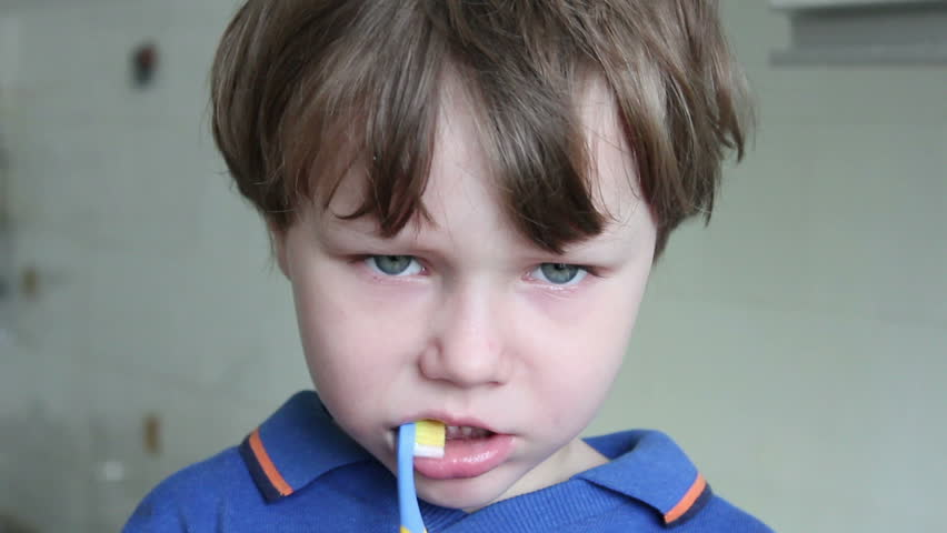 Boy brushing his teeth with a brush