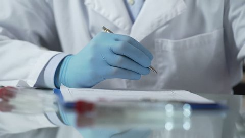 Lab worker filling in test results forms, holding plastic tube with HIV sample