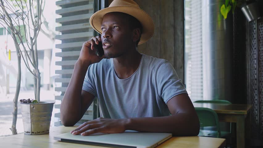 Cheerful and lively young business man with dark skin has an important start up deal conversation through the conference call on his smartphone with a success and confidence on his face. | Shutterstock HD Video #26240132