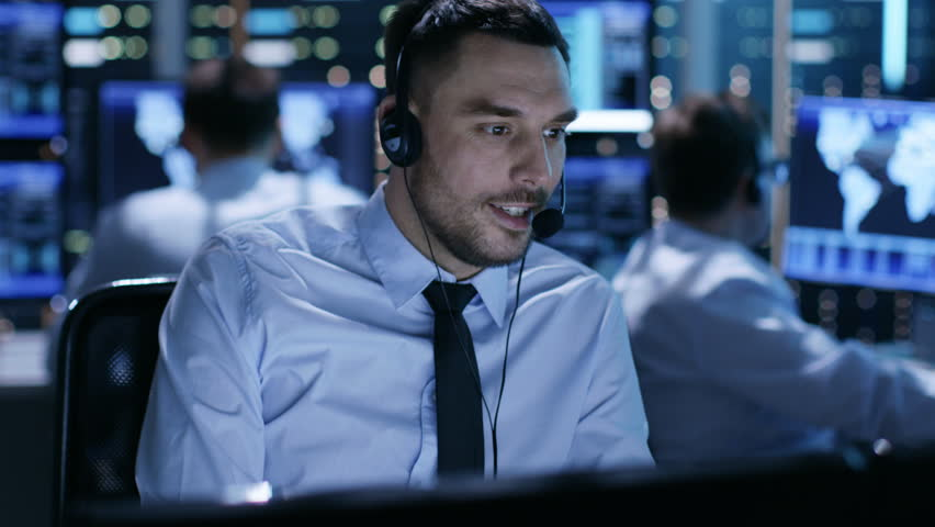 In System Control Center Technical Support Specialist Speaks into Headset. His Colleagues are Working in the Background in a Room Full of Screens.