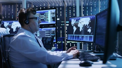 Camera Flies Actively Through System Control Center Showing Professional Security Personnel Working at Their Workstations With Multiple Displays.  Shot on RED EPIC-W 8K Helium Cinema Camera.