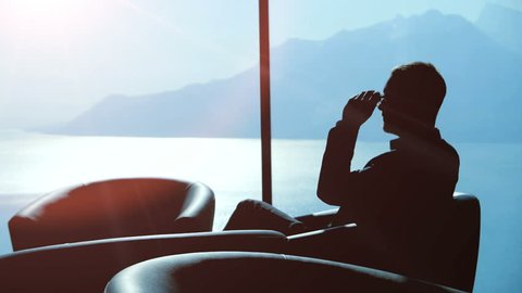 silhouette of businessman with glasses sitting in office lobby looking through the window thinking about finance sales ideas
