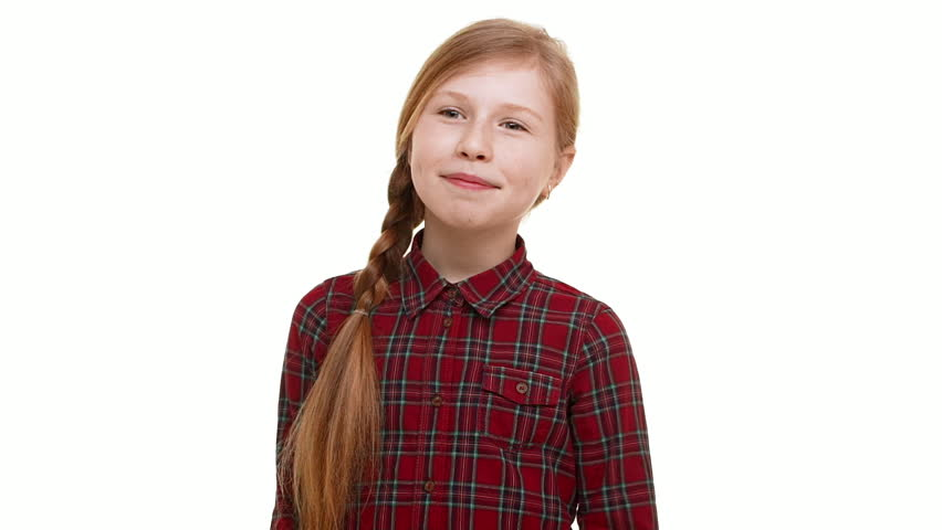 Cute lovely Caucasian elementary-school aged girl clamly standing on white background with little smile in slowmotion