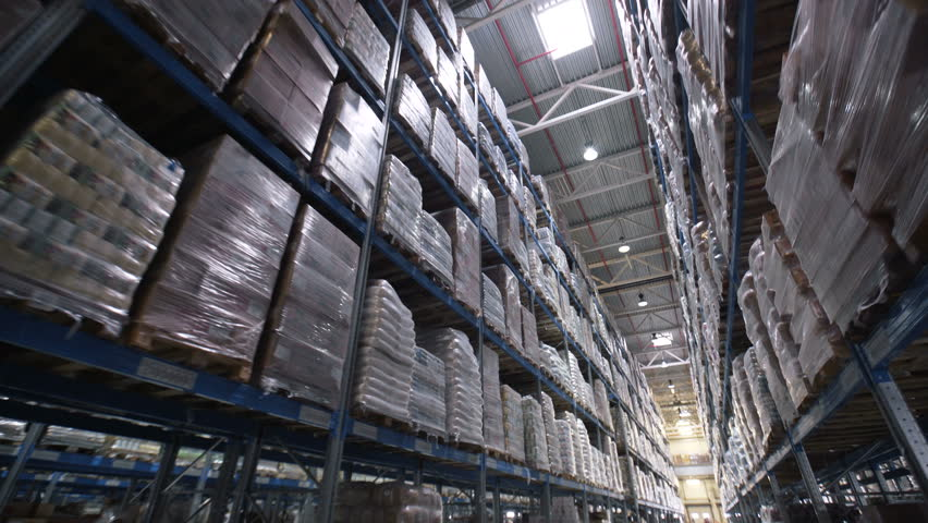Camera moves up on shelves of cardboard boxes inside a storage warehouse. Large warehouse logistics terminal. Industrial stock with boxes