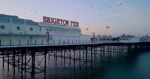 Brighton Pier Aerial view at sunrise. Early morning sunrise at the iconic Pier in Brighton with seagulls flying in 4k.