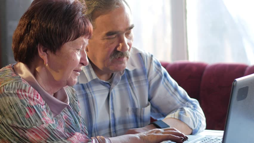 An elderly couple is sitting at home at the laptop. A woman reads news, a man with a mustache sits next to him and talks | Shutterstock HD Video #26312399