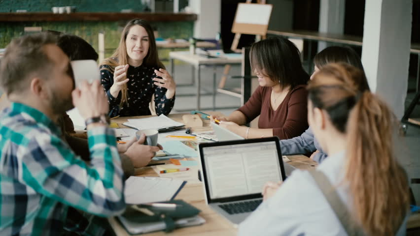 Multiethnic group of people in modern office. Creative business team working on project together, laughing and smiling.