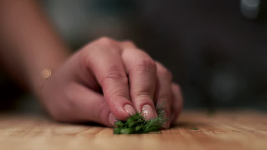 Woman with knife cuts bunch of fresh dill on wooden board. Close up of fresh cut fennel on wooden board. Close up of cut fresh dill on wooden board. Preparation salad. Food ingredients. Cooking food