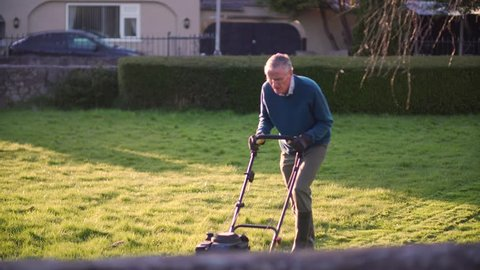 Senior man mowing the lawn grass, landscaping in garden the evening sun Summer. Calm, relaxing gardening for retired pensioner mature male. White Caucasian in 60's / 70's. Mover equipment work / hobby