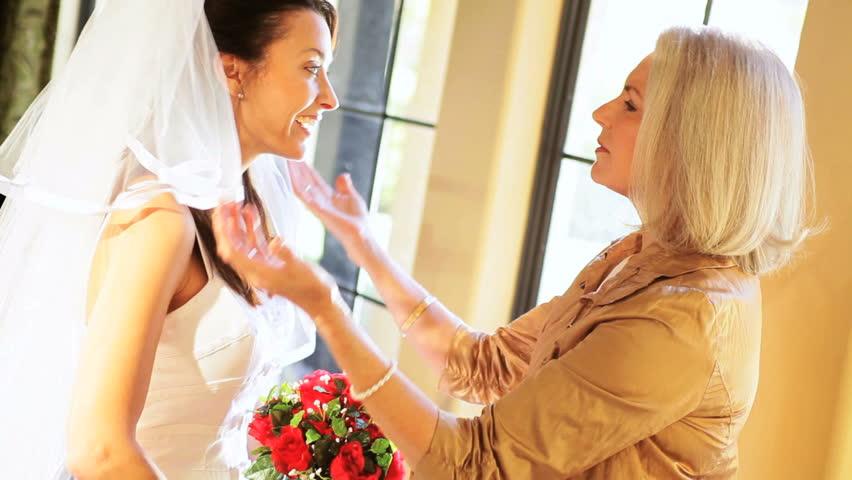 Brides mother reassuring daughter before wedding ceremony