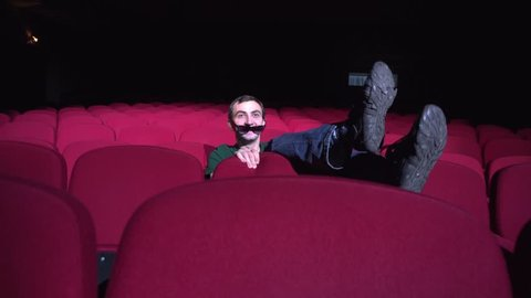 One man sitting in comfortable red chairs in dark cinema theater Looks comedy and laughs