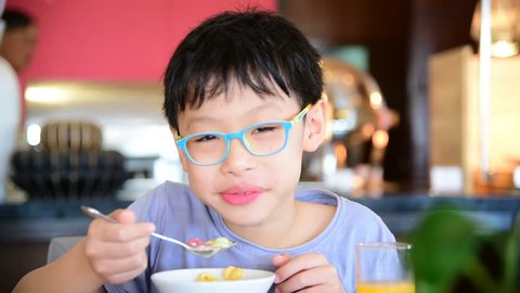Young asian Boy eating cereal with milk