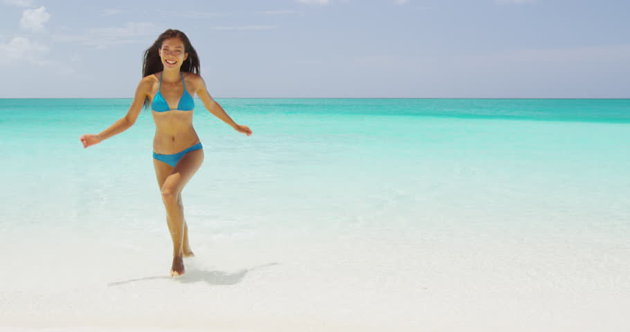 Beach bikini woman running out of sea laughing happy after swimming in the ocean on vacation travel getaway holidays. Beautiful young multiracial Asian Caucasian female model. RED EPIC SLOW MOTION,