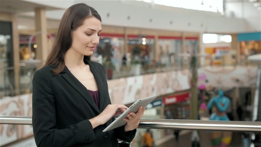 Young female passenger traveller at the airport using her tablet computer while waiting for flight, business woman after work in office in shopping mall use tablet pc | Shutterstock HD Video #26413772