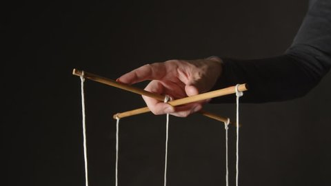 MANIPULATION: Hand of a puppeteer