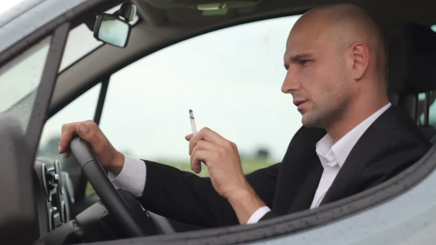 Young businessman smoking cigarettes in car | Shutterstock HD Video #2643272