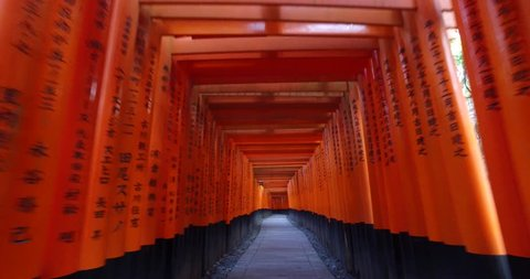 POINT OF VIEW: Walking inside Fushimi Inari Shrine or Fushimi Inari Taisha, a Shinto shrine in Kyoto, Japan. A Japanese monument, famous for its thousands of vermilion torii gates.
