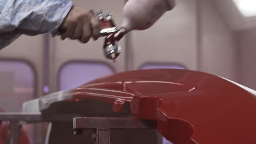 Footage of a car panel being painted in a painting chamber 2
